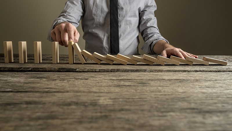 Front view of a businessman stopping domino effect with his fing
